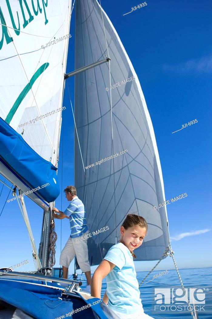 Stock Photo: Father and daughter 8-10 on deck of sailing boat, man standing beside sails, focus on girl in foreground, smiling, portrait.