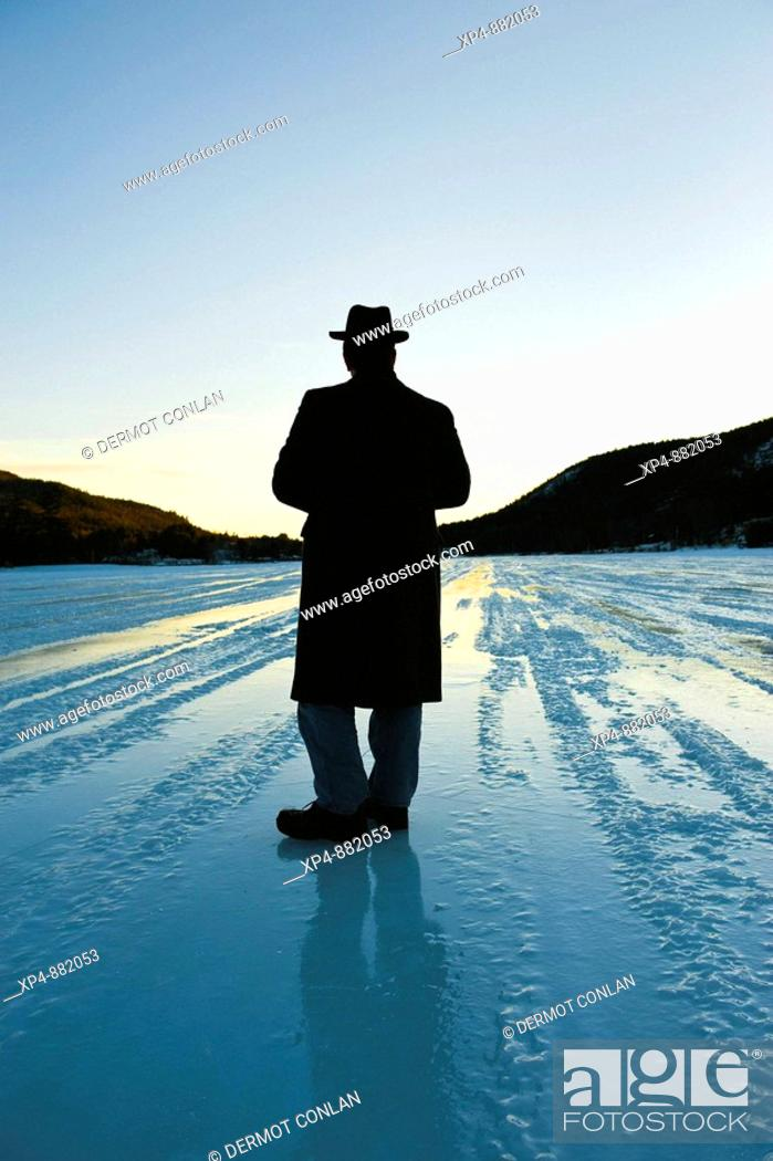 Stock Photo: Silhouette of a man wearing an overcoat and a hat standing on a frozen lake strating off to the horizon, his back is to the camera.