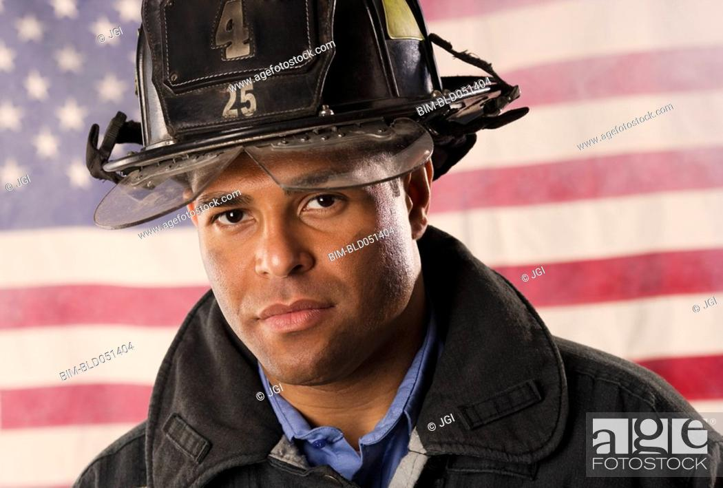Stock Photo: Hispanic male firefighter in front of American flag.