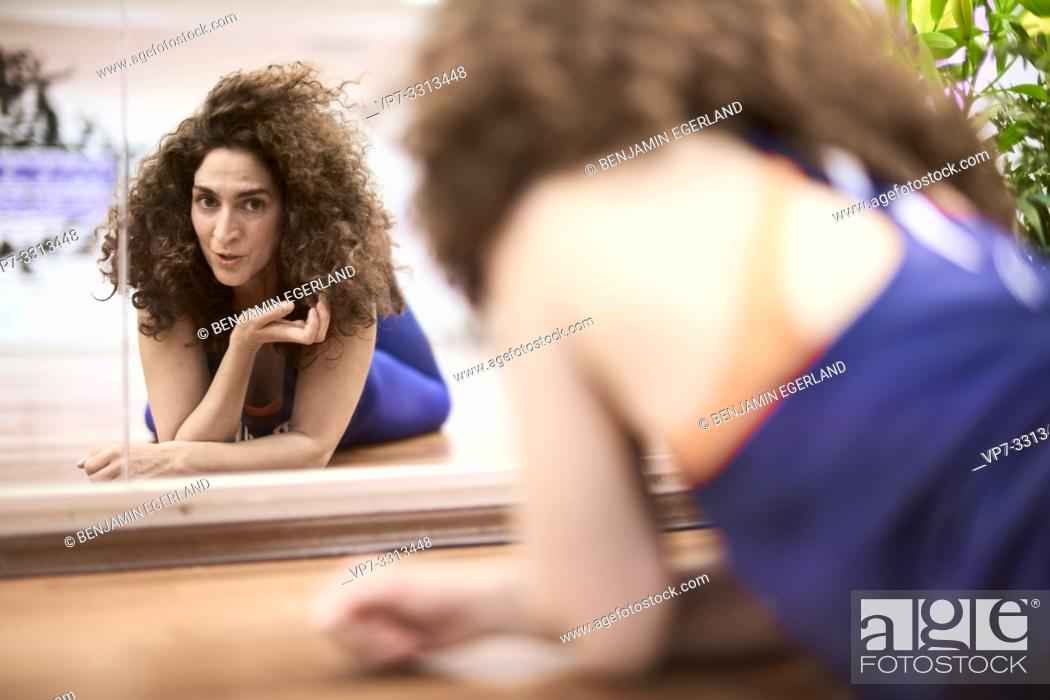 Imagen: sporty mature woman laying on floor in fitness studio, looking at herself in mirror.