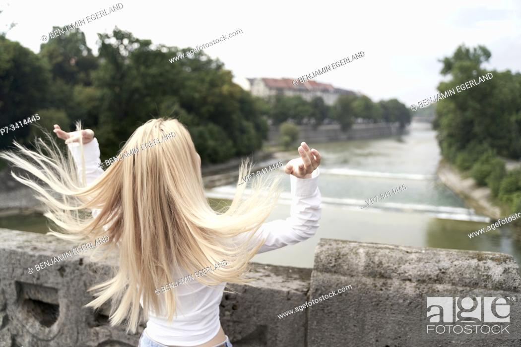 Photo de stock: woman shaking hair on bridge over river Isar in Munich, Germany.