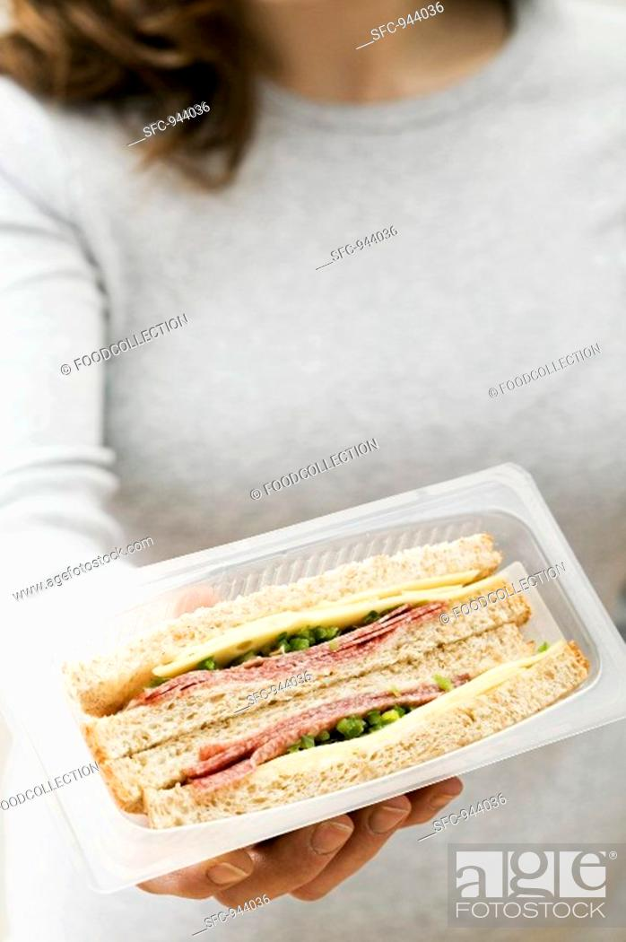 Stock Photo: Woman holding two salami & cheese sandwiches in packaging.