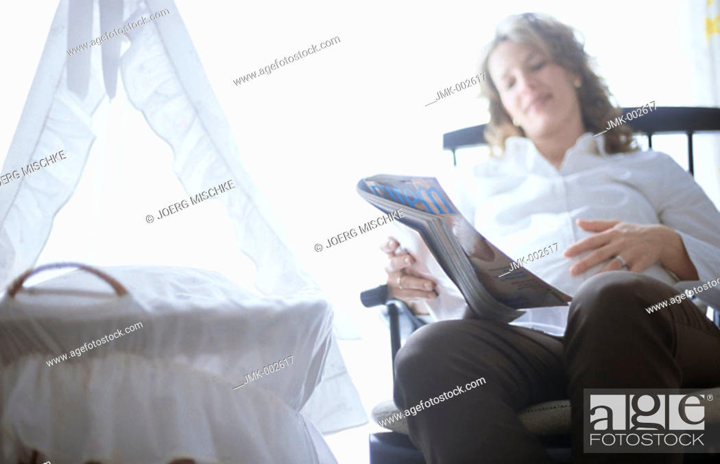 Stock Photo: A young pregnant woman, 25-30 30-35 35-40 years old, sitting in a rocking chair in the nursery, next to the cradle, reading.