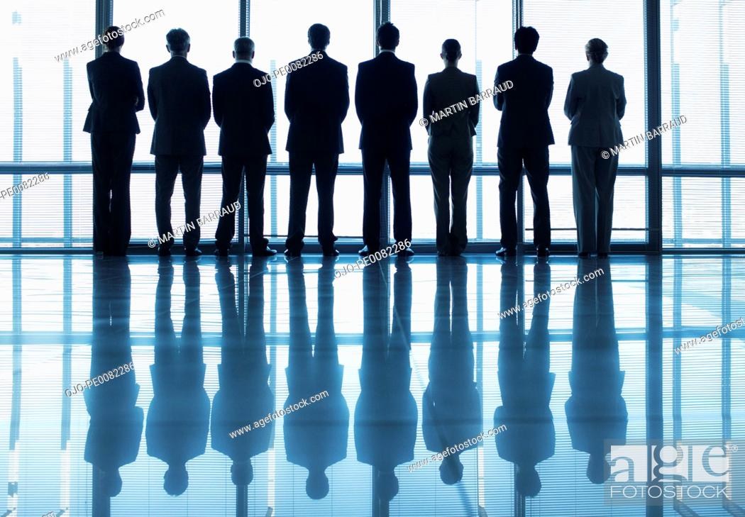 Stock Photo: Silhouette of business people in a row looking out lobby window.