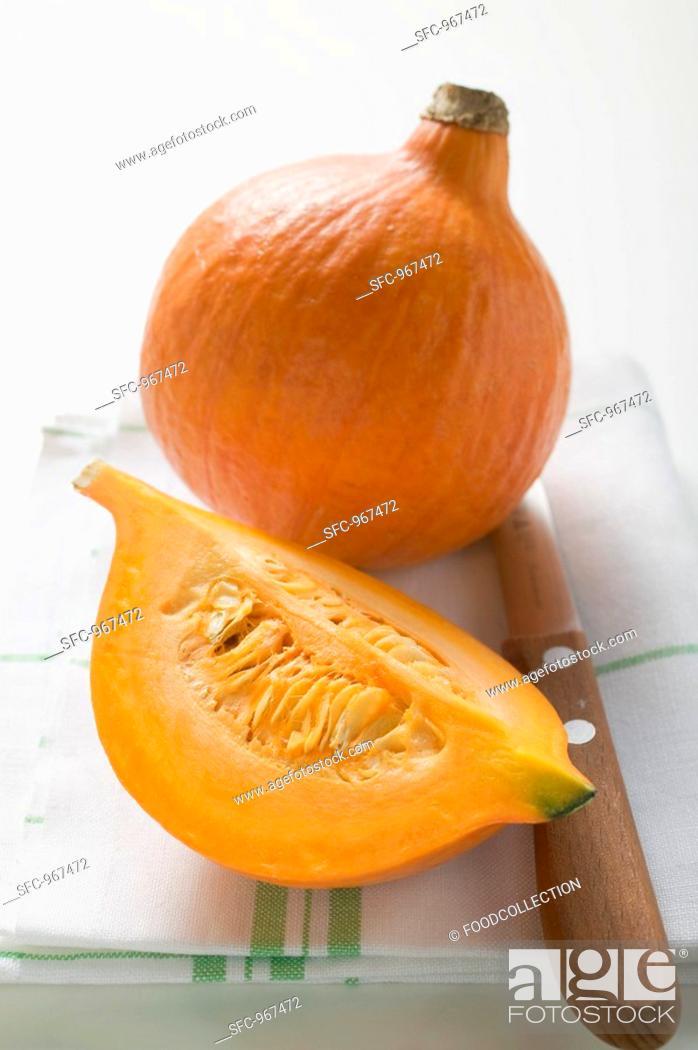 Stock Photo: Hokkaido pumpkins whole and quarter on tea towel, knife.