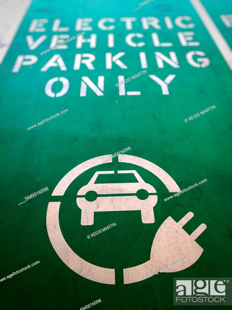 Stock Photo: Electric vehicle parking only sign painted on the ground of a parking spot.