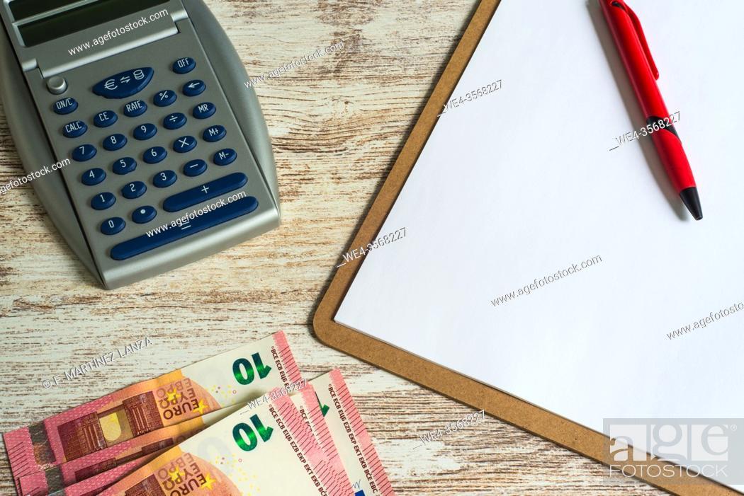 Stock Photo: Folder with a calculator and ten-euro notes.
