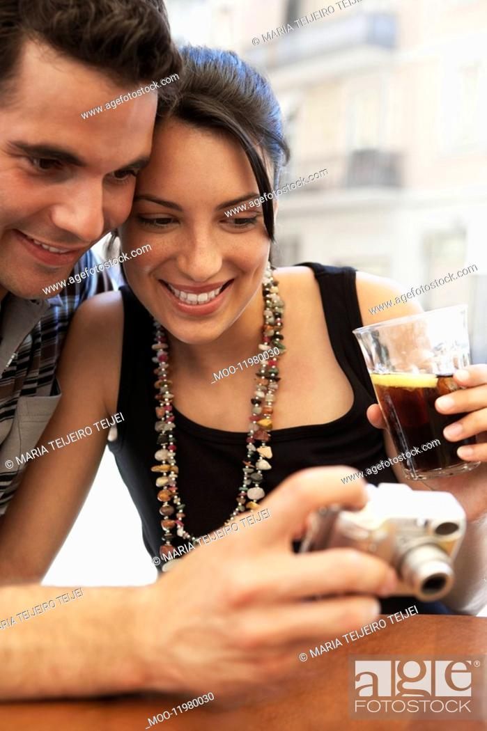 Stock Photo: Young couple at cafe looking at camera together portrait.
