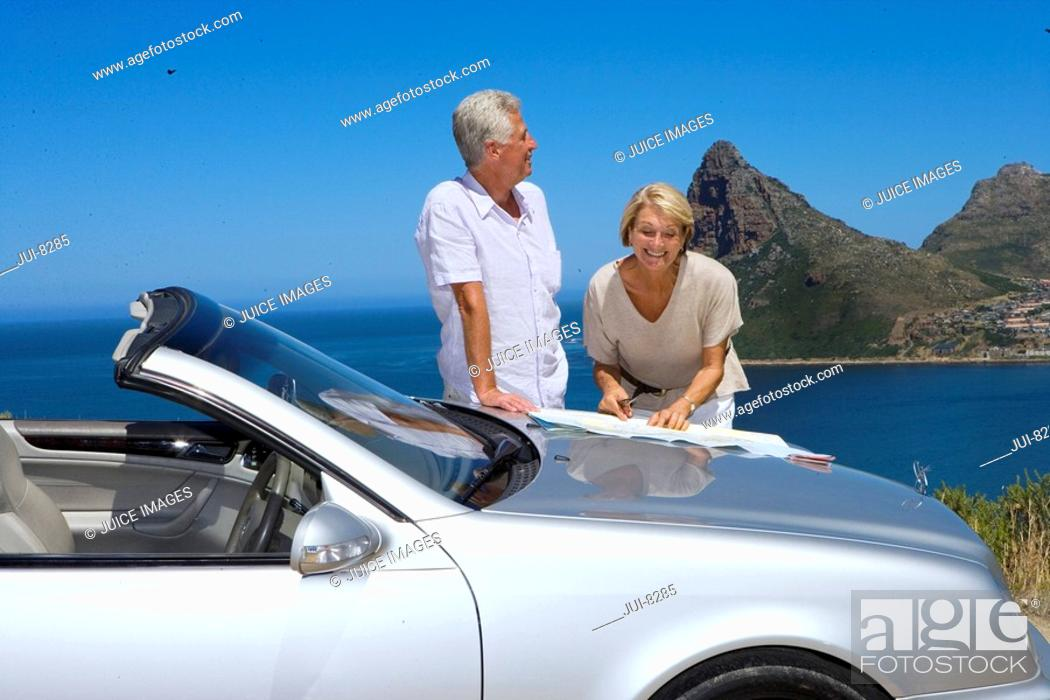 Stock Photo: South Africa, Cape Town, senior couple standing by car with map, smiling, sea in background.