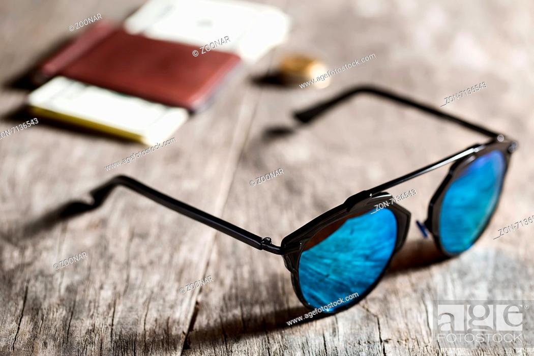 Stock Photo: Stylish sunglasses with blue tinted mirror on textured wooden background.