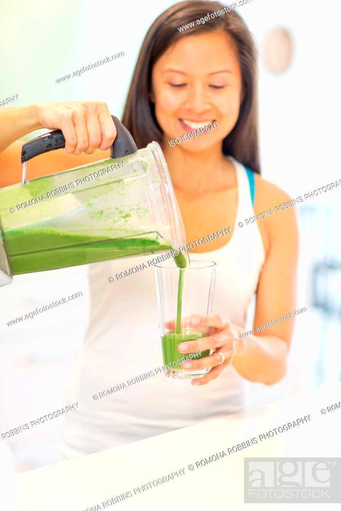 Imagen: Mid adult woman pouring green smoothie in kitchen.