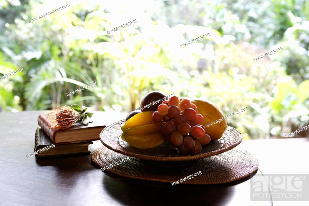 Stock Photo: Close-up of fruit and books kept on a table.