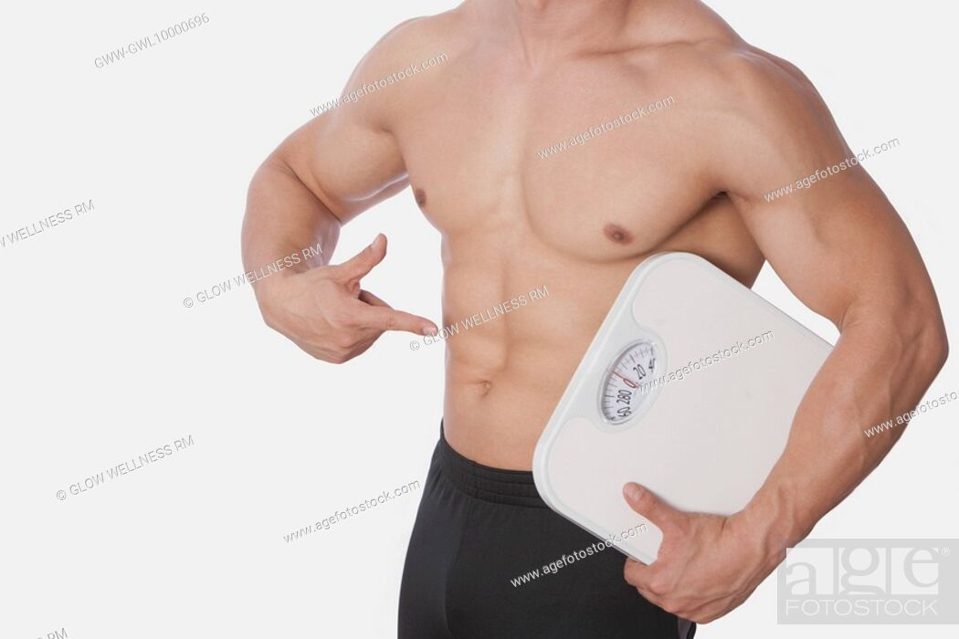 Imagen: Mid section view of a man holding a bathroom scale and showing his abdomen.