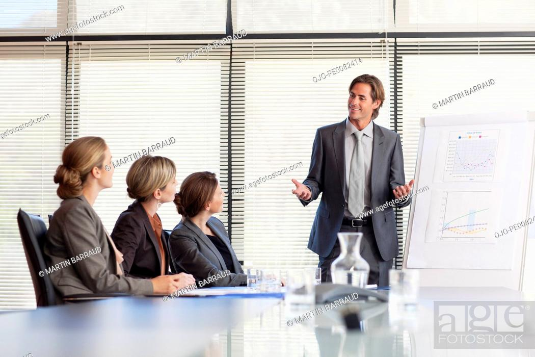 Stock Photo: Businessman leading meeting in conference room.