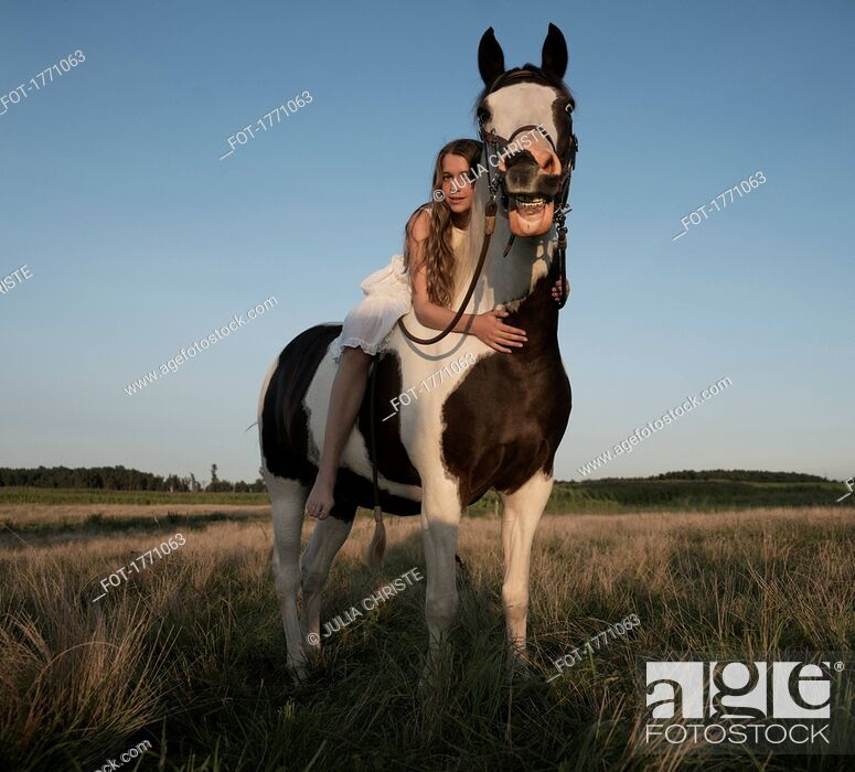 Stock Photo: Portrait girl laying on horse in rural field.
