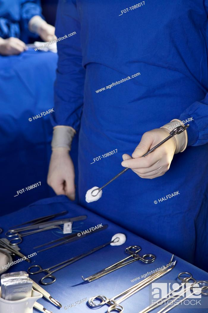 Stock Photo: Midsection of a man holding a surgical instrument.