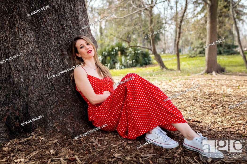 Imagen: Young smile blond woman sitting near tree with red long dress.