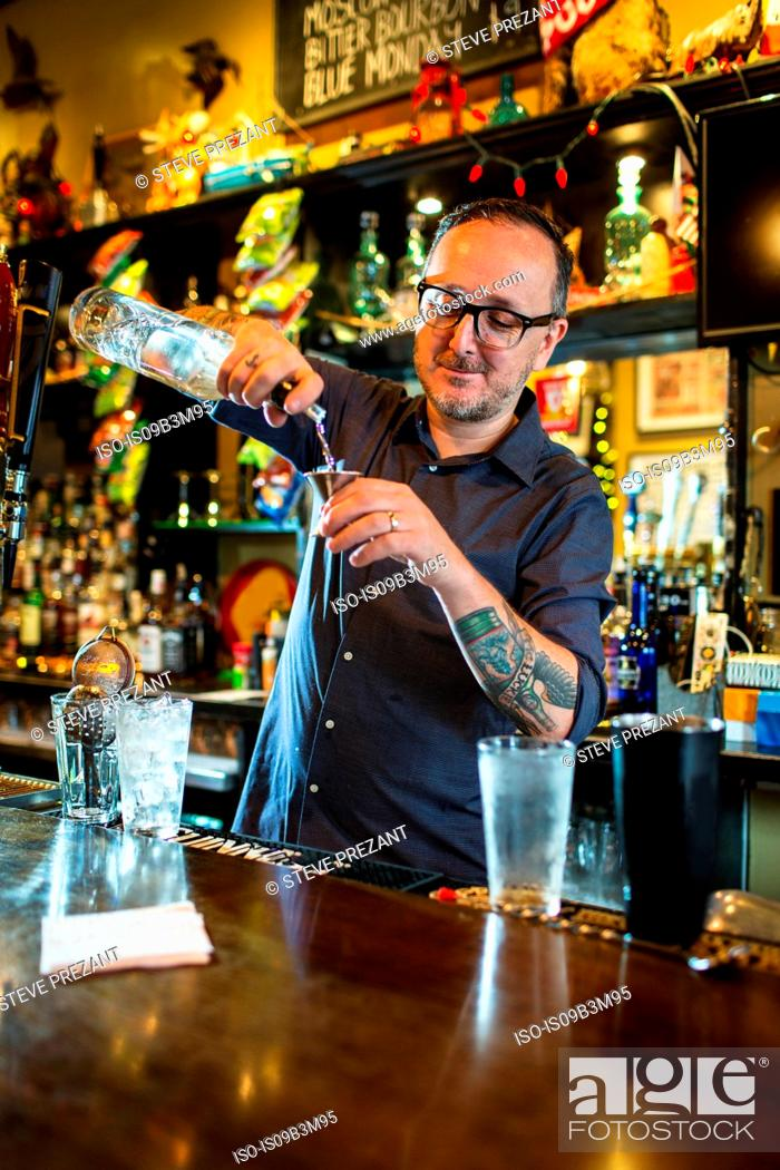 Stock Photo: Barman preparing cocktail at public house counter.