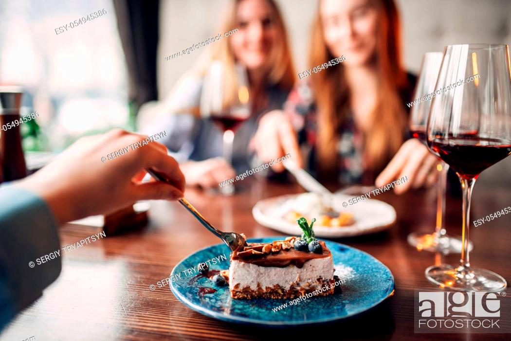 Stock Photo: Young women eats sweet cakes in restaurant. Chocolate dessert and alcohol on the table.
