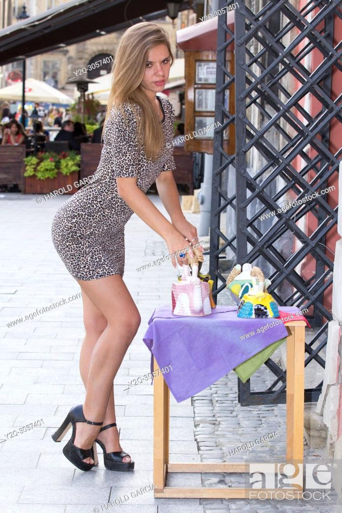 Stock Photo: Sexy Ukrainian woman wearing a leopard skin print dress posing on the street with a tea pot for a photographic sequence in the ancient city of Lviv, Ukraine.