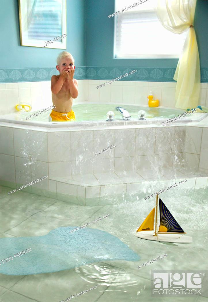 Stock Photo: 4 year old boy overflowing bathtub.