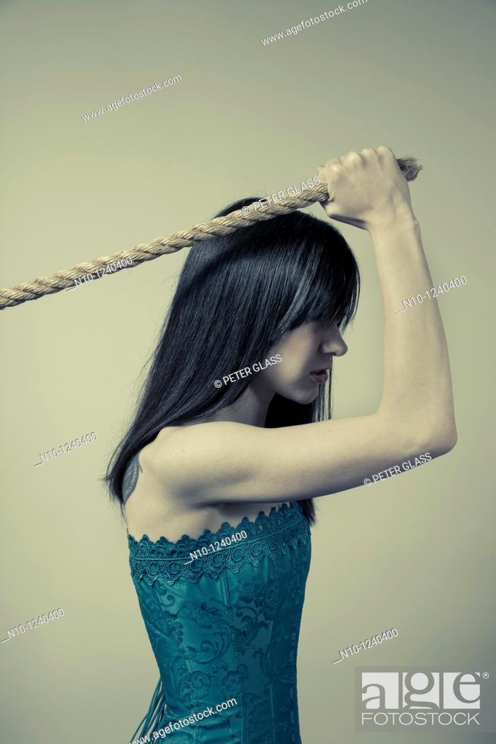 Stock Photo: Young woman pulling on the end of a rope.