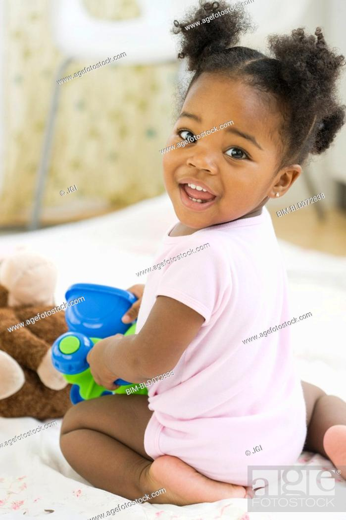 Stock Photo: African American girl playing with toy.