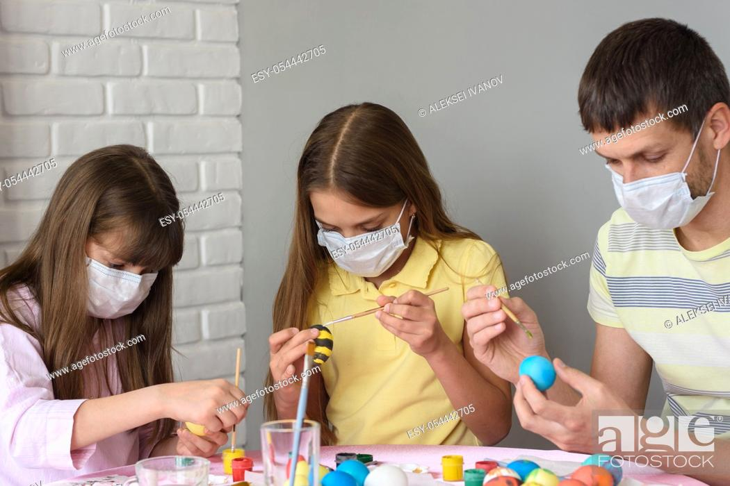 Stock Photo: Ill children and dad paint Easter eggs for Easter.