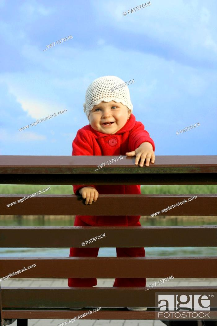 Stock Photo: Happy one year girl on a bench.