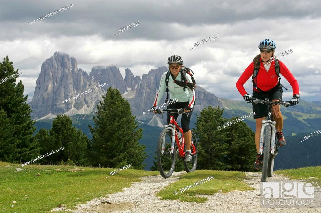 Stock Photo: Female mountain bikers, Mts. Langkofel and Plattkofel in the background, Dolomites, Northern Italy, Europe.