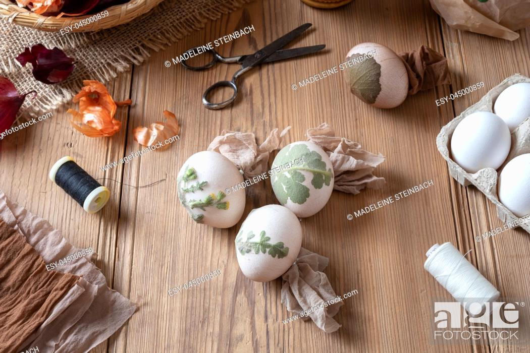 Stock Photo: Preparation of Easter eggs for dying with onion peels with a pattern of herbs and flowers.