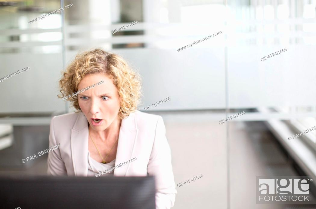 Stock Photo: Surprised businesswoman working in office.