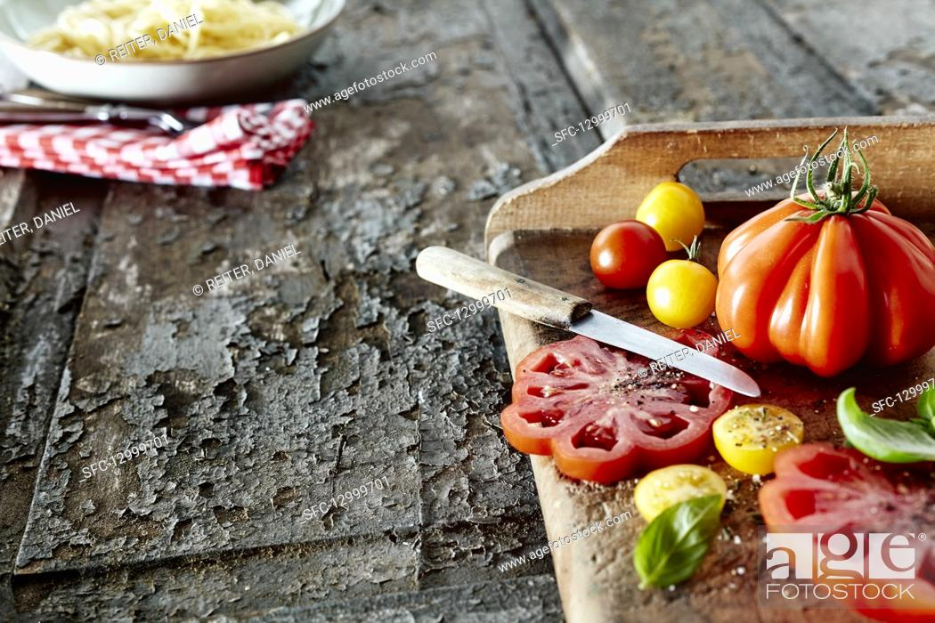 Photo de stock: Various heirloom tomatoes with salt, pepper and basil.