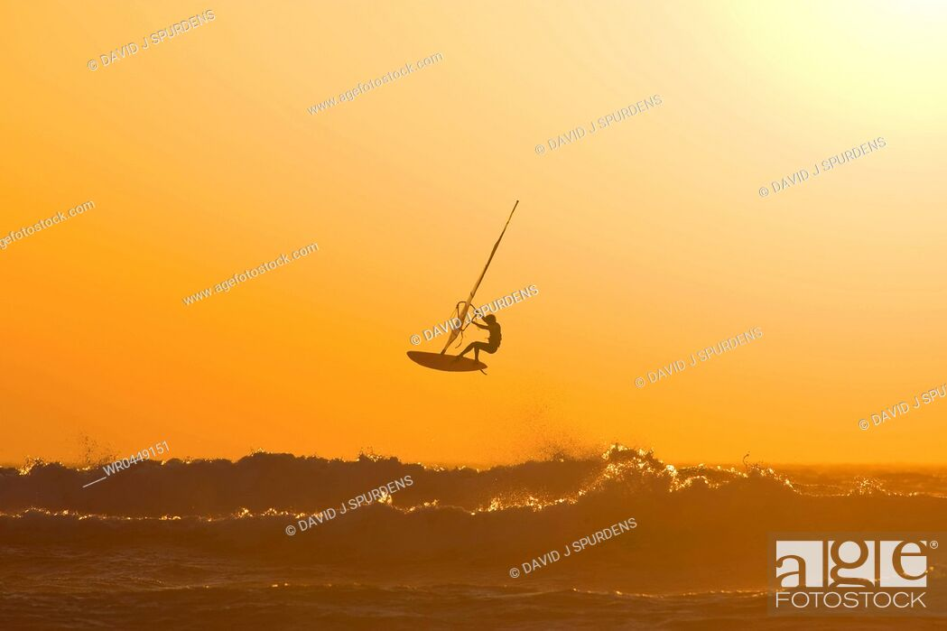 Stock Photo: A windsurfer jumps of a wave into the sunset.