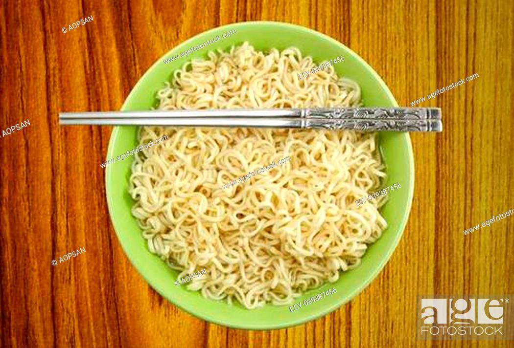 Stock Photo: Noodles in bowl and chopsticks on wood background.