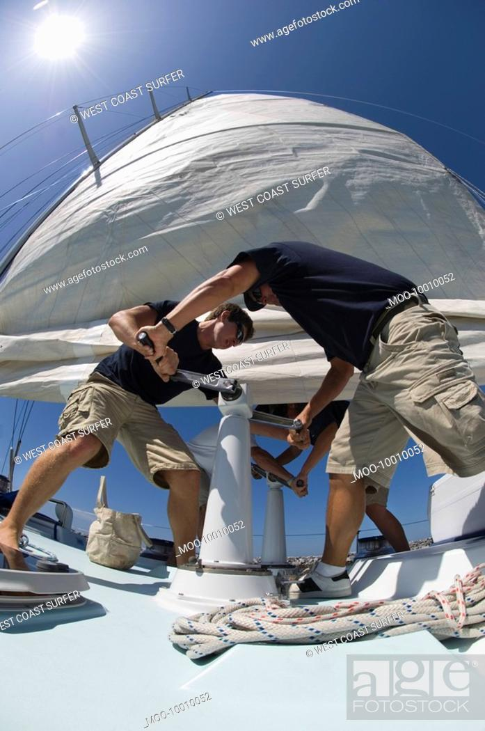 Stock Photo: Sailors operating windlass on yacht low angle view wide angle lens.