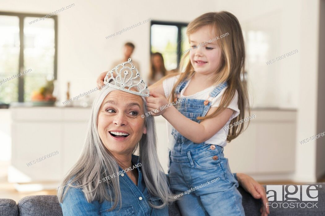 Stock Photo: Granddaughter putting crown on grandmothes head.