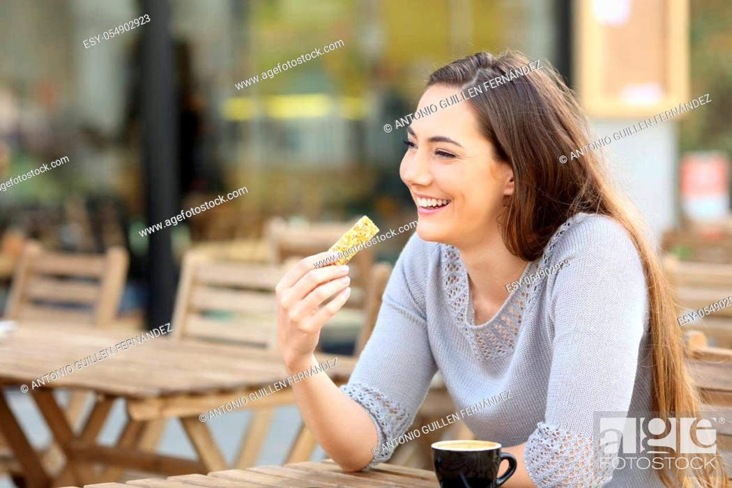 Stock Photo: Happy young woman holding a cereal snack bar sitting on a cafe terrace.
