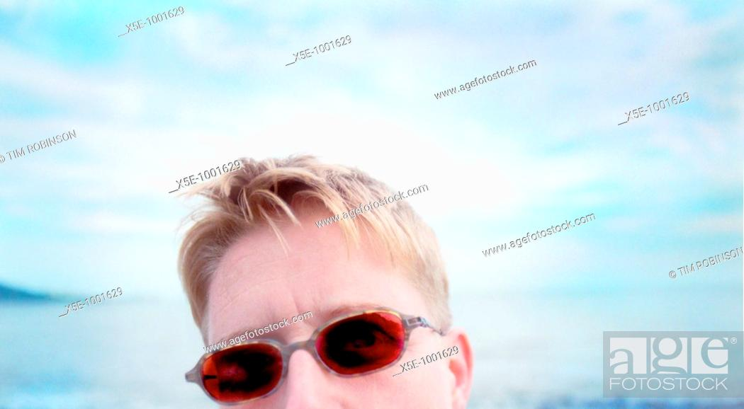 Stock Photo: Partial face of blonde woman wearing red sunglasses at beach.