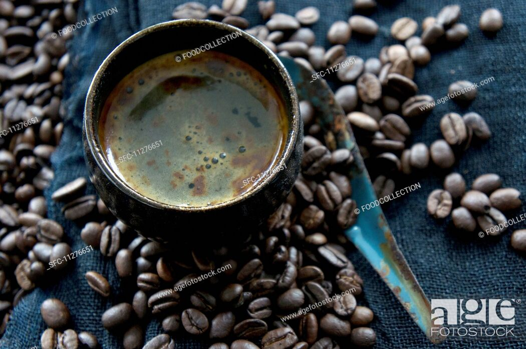 Stock Photo: A coffee cup on coffee beans with a rusty spoon.