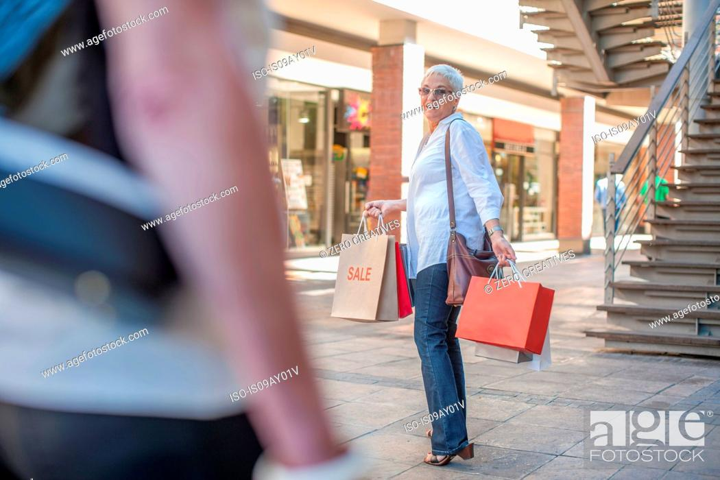 Stock Photo: Mature woman shopper waiting for friend in shopping mall.