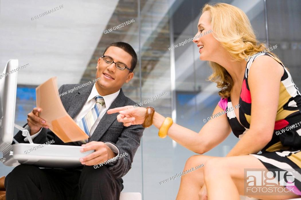Stock Photo: Businessman showing a document to a mature woman sitting beside him.