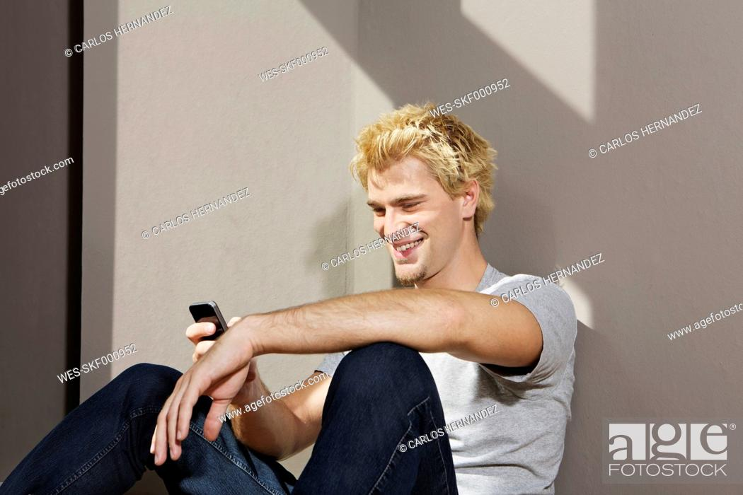 Stock Photo: Germany, Berlin, Young man using smart phone, smiling.