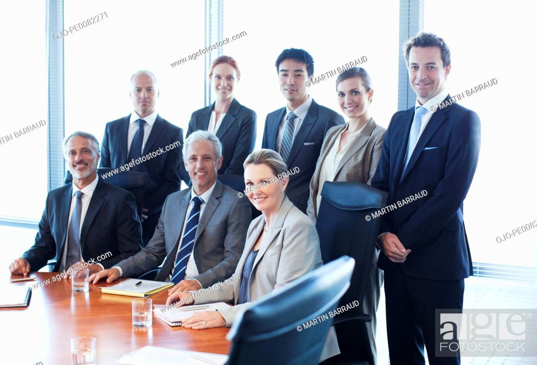 Stock Photo: Portrait of smiling business people in conference room.