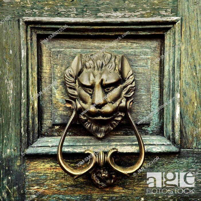 Stock Photo: An antique door knocker is seen hung on the wooden door of a Spanish colonial house in Morelia, Mexico, 2 November 2014.