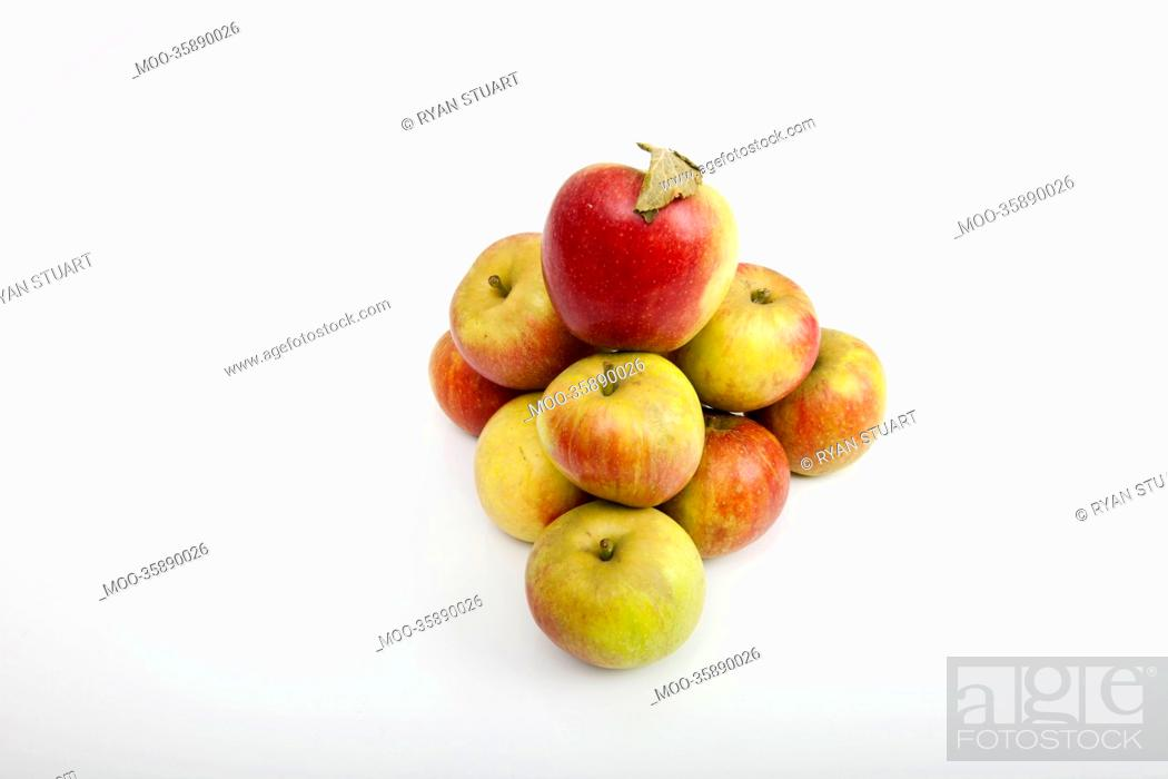 Stock Photo: Fresh apples forming pyramid over white background.