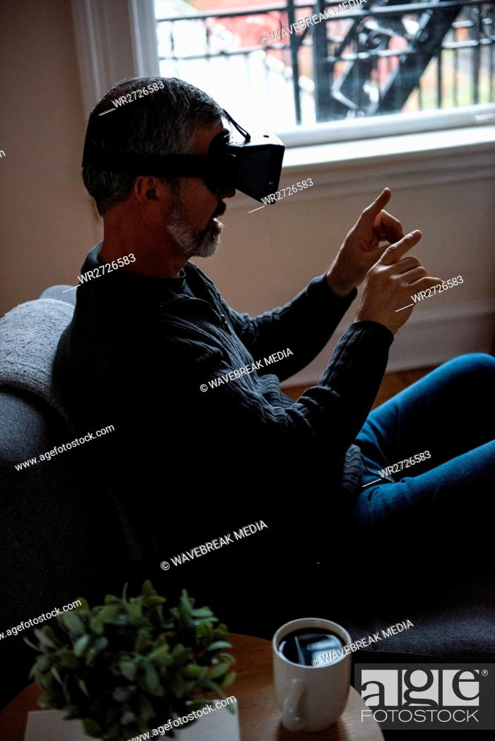 Stock Photo: Man using virtual reality headset in living room.