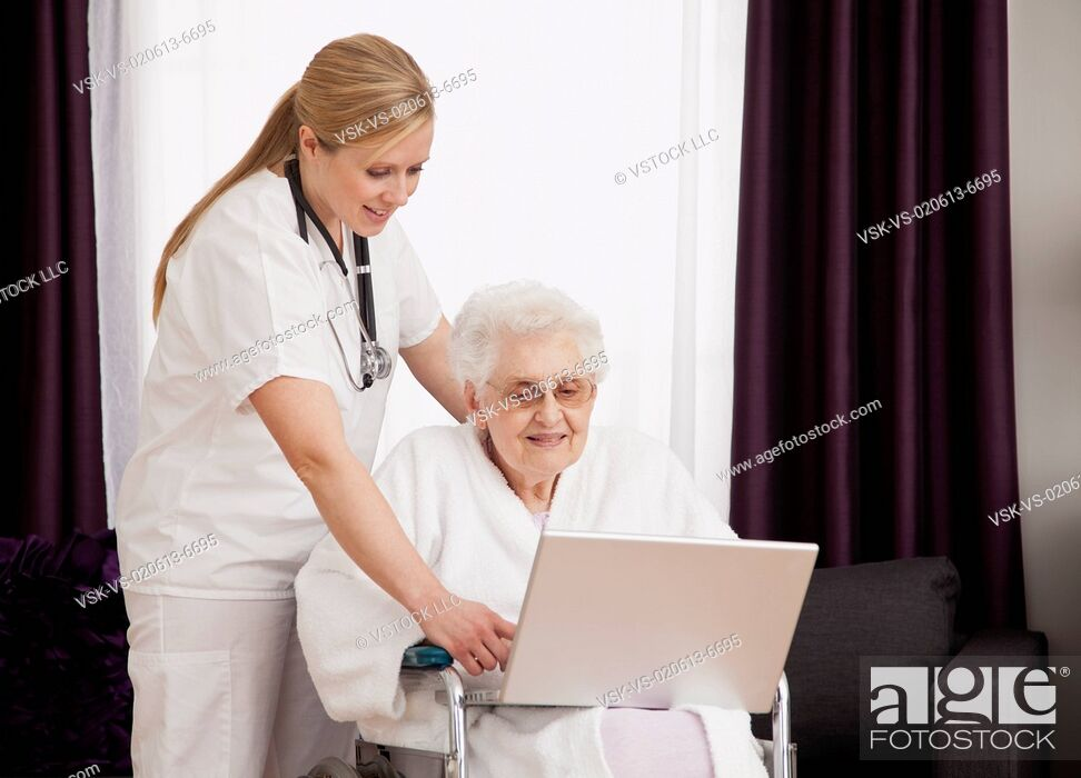 Stock Photo: Nurse helping senior woman on wheelchair in using laptop.