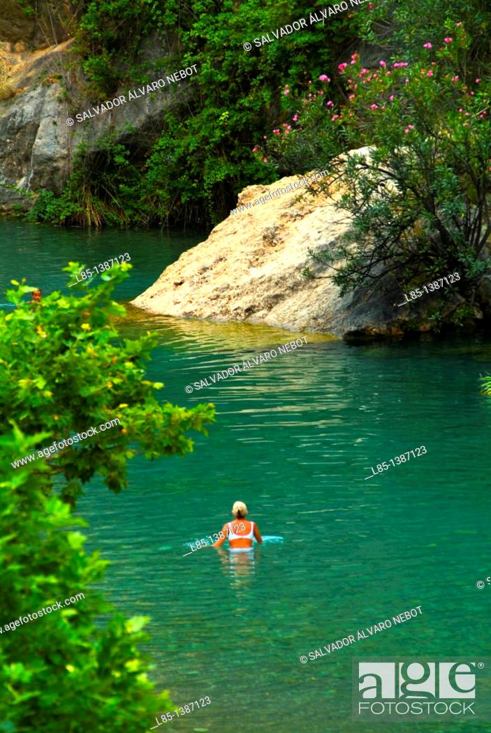 Imagen: Woman bathing in a river in the countryside.