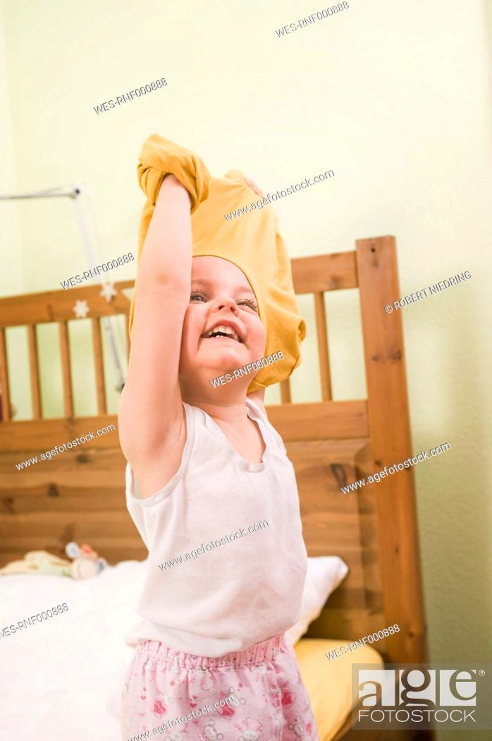 Stock Photo: Girl undressing, smiling.